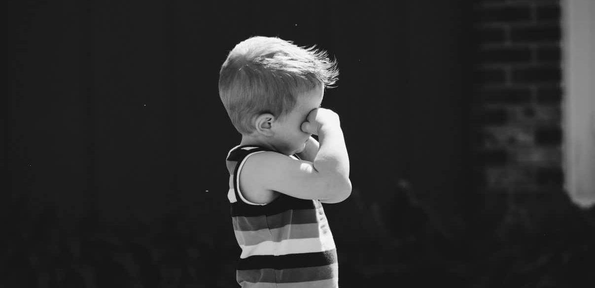 Een jongetje dat zijn tranen wegveegt omdat hij niet mag voelen